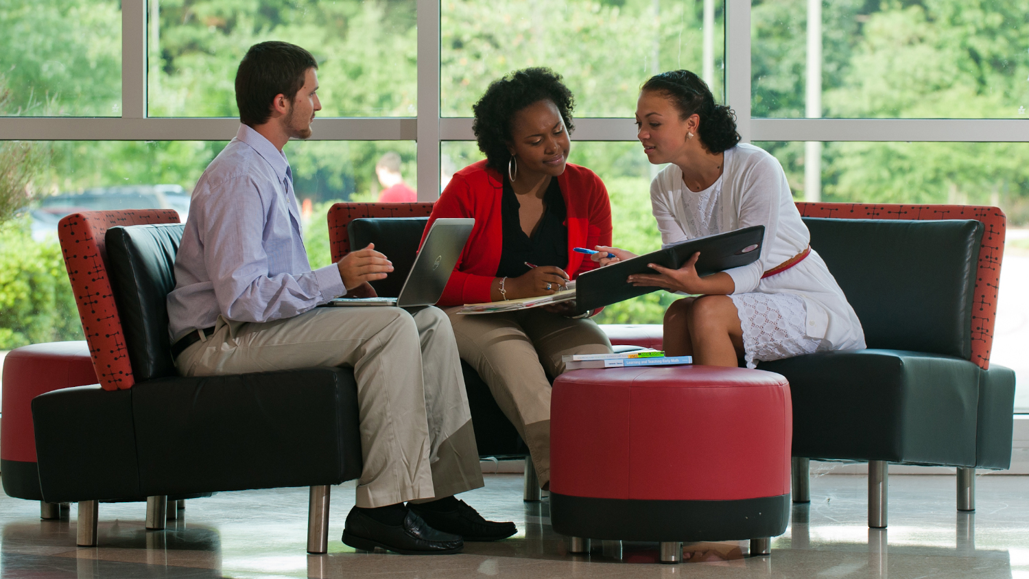 Three working professionals on laptops sit and collaborate on NC State's Centennial Campus.
