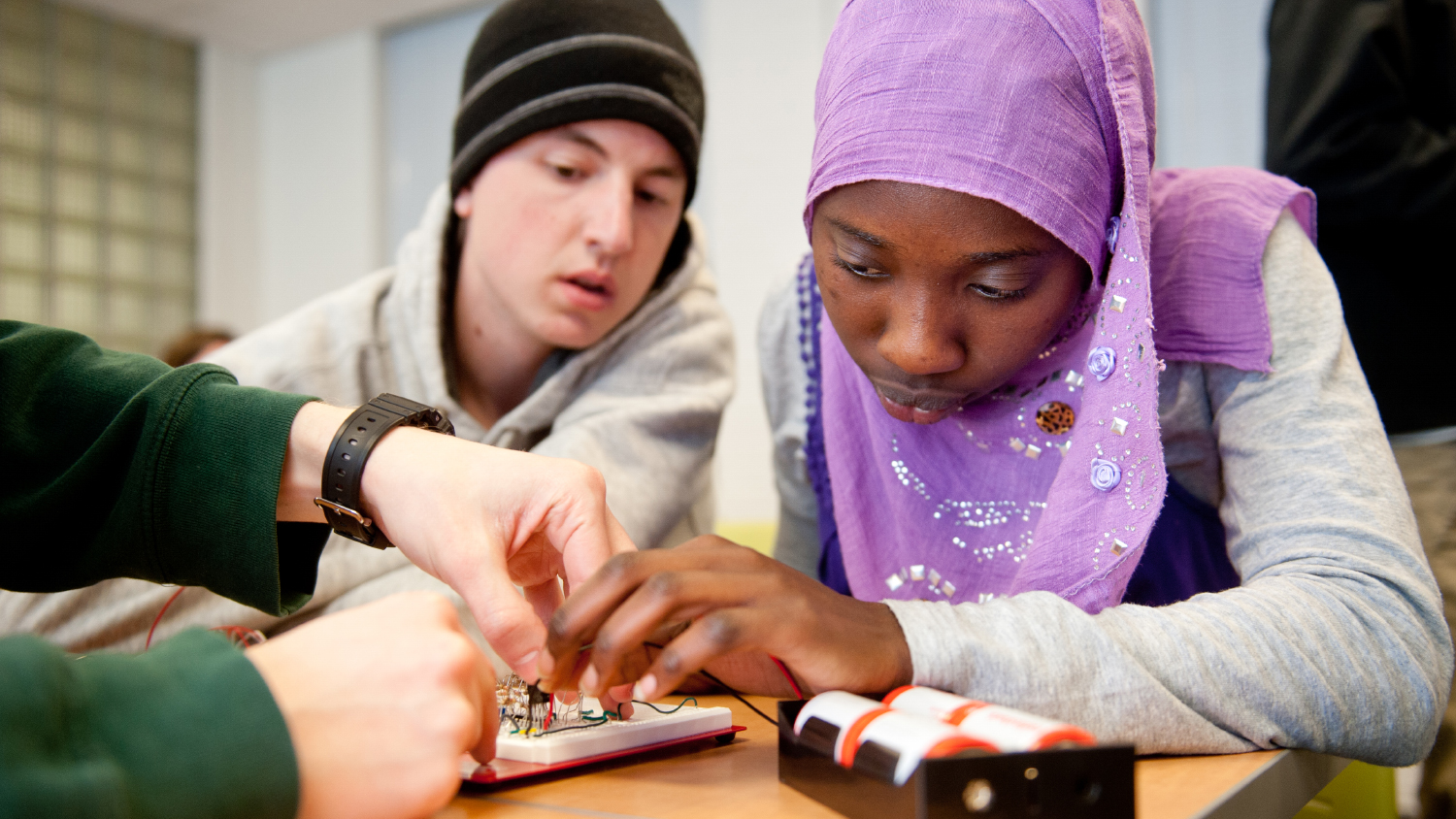 Two young students closely examine a device in a classroom setting.