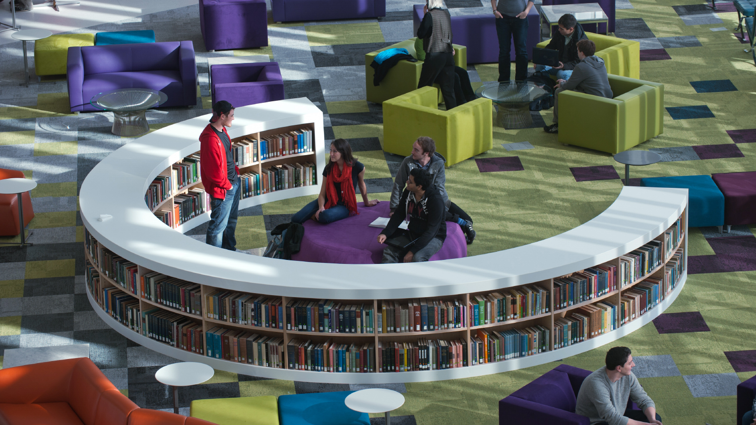 A group of students chat in the colorful atrium of Hunt Library.