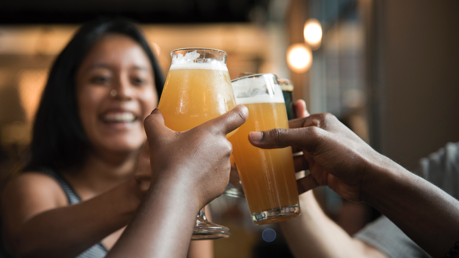 A woman holding a beer toasts with her friends.