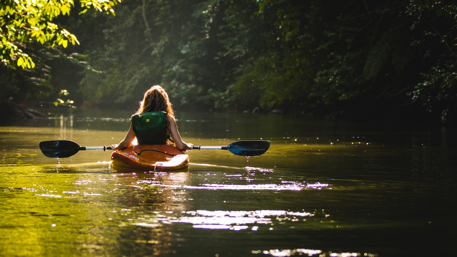 Woman paddling a kayak on smooth water.
