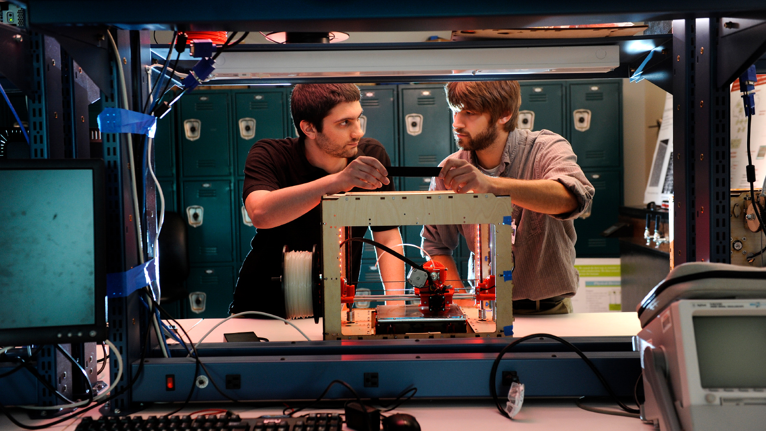 Two students work with a 3D printer on NC State's campus.