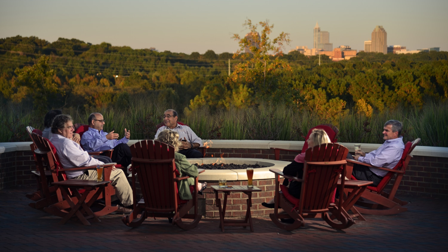 Friends enjoy drinks around the firepit at the Lonnie Poole Golf Course.