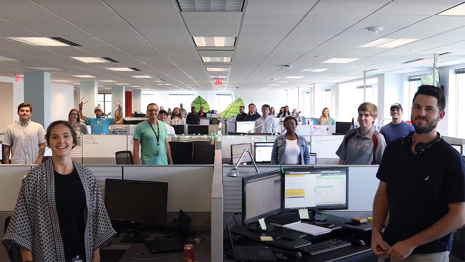 A group portrait of Bandwidth employees standing in their cubicles.