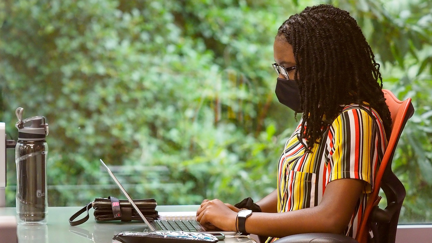A woman studies on NC State's campus while wearing a protective face covering.