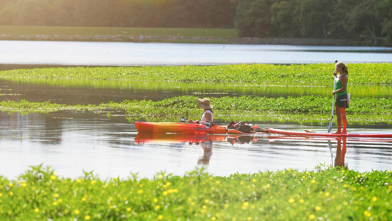 Two women paddling kayaks on Lake Raleigh.